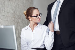Sexy secretary undressing boss in office Royalty Free Stock Photography