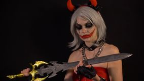 Sexy seductive devil girl makes manicure, cuts nails by sword, celebrate halloween with scary funny pumpkins in darkness stock video