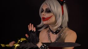 Sexy seductive devil girl makes manicure, cuts nails by sword, celebrate halloween with scary funny pumpkins in darkness stock footage
