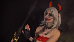 Sexy seductive devil girl makes manicure, cuts nails by sword, celebrate halloween with scary funny pumpkins. Demon stock video