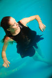 Sexy seductive woman in black dress in water. Sexy seductive woman wearing black dress in swimming pool water. Young attractive alluring girl floating Stock Photos