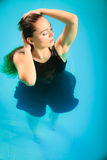Sexy seductive woman in black dress in water. Sexy seductive woman wearing black dress in swimming pool water. Young attractive alluring girl floating Royalty Free Stock Photo