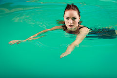Sexy seductive woman in black dress in water. Sexy seductive woman wearing black dress in swimming pool water. Young attractive alluring girl floating Stock Images