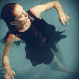 Sexy seductive woman in black dress in water. Sexy seductive woman wearing black dress in swimming pool water. Young attractive alluring girl floating Royalty Free Stock Photography