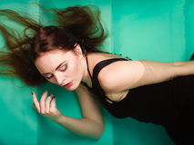Sexy seductive woman in black dress in water. Sexy seductive woman wearing black dress in swimming pool water. Young attractive alluring girl floating. Top view Royalty Free Stock Images