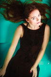 Sexy seductive woman in black dress in water. Sexy seductive woman wearing black dress in swimming pool water. Young attractive alluring girl floating. Top view Royalty Free Stock Photography