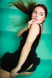 Sexy seductive woman in black dress in water. Sexy seductive woman wearing black dress in swimming pool water. Young attractive alluring girl floating. Top view Stock Image