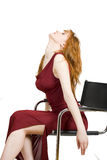 Sexy seductive woman in red dress on a chair Royalty Free Stock Photos