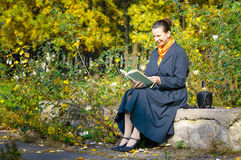 Sexy Senior Woman Reading. A book in the park during a sunny autumn day Royalty Free Stock Image