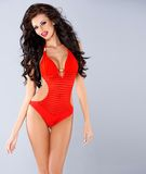 sensual brunette posing in red swimsuit Stock Photos