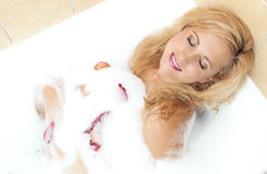 Sexy Sensual Caucasian Blond Female in Foamy Bathtub Filled with Flowery Petals Stock Images