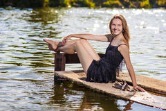 Sexy Sensual Caucasian Blond Woman Sitting on Pier Near Water an Royalty Free Stock Photography