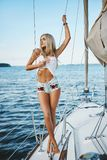 Sensual and fasionable blonde model girl with perfect body in jeans shorts and white t-shirt posing with closed eyes on a yac. Ht ship at the sea royalty free stock photography