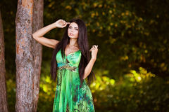 Sexy sensual very beautiful brunette girl in a green dress stand. Ing near a tree in the summer Stock Images