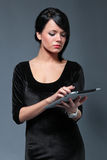 serious brunette with new made touch pad Royalty Free Stock Images