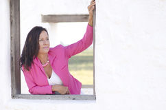 Sexy serious mature woman in pink outdoor Stock Photography