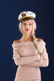 Sexy ship captain. Sexy blonde with long hair in a beautiful dress and captain's cap Royalty Free Stock Photography