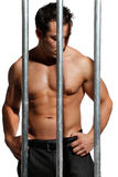 Sexy shirtless man behind bars on white background Stock Photography