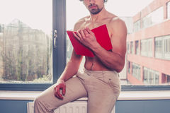 Sexy shirtless man reading by window Stock Photos