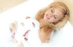 Sexy sinnliche kaukasische blonde Frau in der schäumenden Badewanne gefüllt mit den blumigen Blumenblättern Stockbilder
