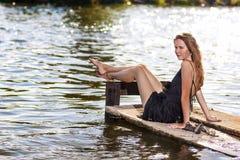 Sexy sinnliche kaukasische blonde Frau, die auf Pier Near Water sitzt r Lizenzfreie Stockfotos