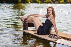 Sexy sinnliche kaukasische blonde Frau, sitzend auf Pier Near Water Lizenzfreie Stockfotografie