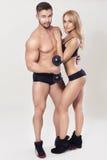 Sexy Sitz mischte Paare in der Sportkleidung auf neutralem grauem Hintergrund mit Lizenzfreies Stockfoto