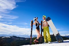 Sexy skier woman in bikini and snowboarder man with bare torso on background of snowy mountains.