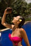 Sexy slank donkerbruin jong wijfje die water geven met verse kokosmelk in pool met kristal blauw water Koninklijke tropische toev royalty-vrije stock afbeelding