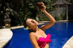 Sexy slank donkerbruin jong wijfje die water geven met verse kokosmelk in pool met kristal blauw water Koninklijke tropische toev stock afbeelding