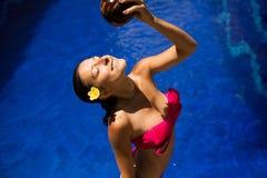 Sexy slank donkerbruin jong wijfje die water geven met verse kokosmelk in pool met kristal blauw water Koninklijke tropische toev royalty-vrije stock foto's