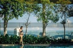 Sexy slank Kaukasisch brunette die tussen groene struiken en bomen op rand van zwembad op dak met cityscape lopen stock foto's