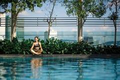 Sexy slanke Kaukasische donkerbruine meditatie tussen groene struiken en bomen op rand van zwembad op dak met cityscape stock fotografie