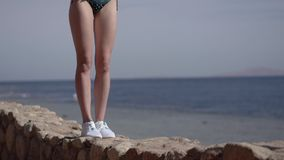 Sexy legs of model in bikini stands on the stone of the beach in slow motion. stock footage