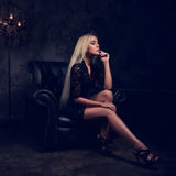 Sexy slim blond model sitting in fashion armchair in black dress Stock Image