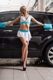 slim blonde in formula 1 style at carwash royalty free stock images