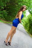 Slim brunette. Brunette in blue dress on the road stock photography