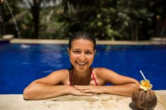 slim brunette young female posing with fresh coconut in pool with crystal blue water. Royal tropical resort relax stock photos