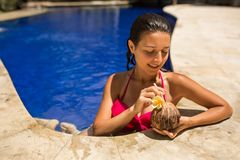 slim brunette young female posing with fresh coconut in pool with crystal blue water. Royal tropical resort relax royalty free stock photo