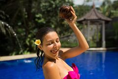 slim brunette young female watering herself with fresh coconut milk in pool with crystal blue water. Royal tropical resort stock photos