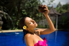 slim brunette young female watering herself with fresh coconut milk in pool with crystal blue water. Royal tropical resort royalty free stock images