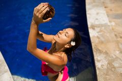 slim brunette young female watering herself with fresh coconut milk in pool with crystal blue water. Royal tropical resort stock photo