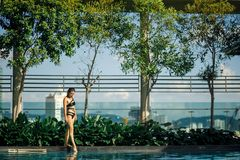 Sexy slim caucasian brunette walking between green bushes and trees on edge of swimming pool on rooftop with cityscape stock photos