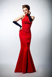 Sexy slim female in sensual red long dress posing Royalty Free Stock Photography