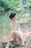 Sexy slim lady wear tight short white dress, sitting on sidewalk Stock Photos