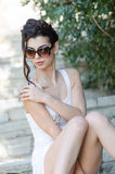 Sexy slim lady wear tight short white dress and sunglasses Royalty Free Stock Photo