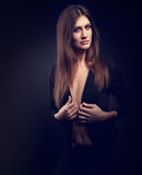 Slim model posing in black jacket with long straight hair s. Tyle on dark background. Fashion portrait. Toned portrait in darkness royalty free stock photography