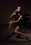 Sexy slim model sitting in fashion armchair and posing in black Royalty Free Stock Images