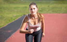 Sexy slim woman running on stadium at sunny day Stock Image