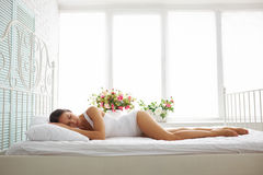 Sexy slim woman in white underwear sleeping on bed with white sh Stock Photo